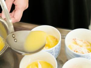 器に、サイコロ状に切った絹ごし豆腐とカニのほぐし身を入れて、卵液を注ぎ入れる。