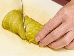 ロールキャベツを鍋から取り出し、斜めに包丁を入れて半分に切り分け、中が見えるようして器に盛り付ける。